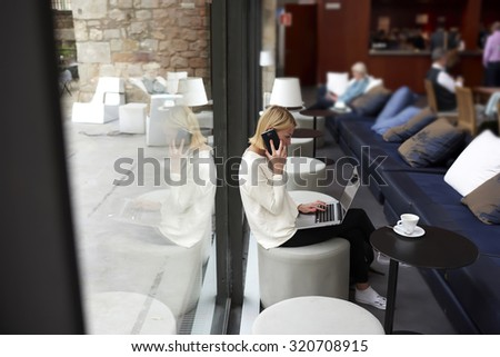 Young businesswoman sitting front open laptop computer and talk on smart phone, female person using net-book during morning breakfast in modern coffee shop, freelancer working on the distance in cafe - stock photo