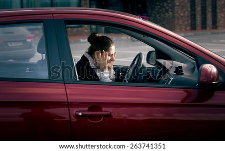 Young businesswoman sitting in car and screaming of fear - stock photo