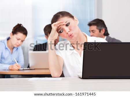 Young Businesswoman Sitting In Front Of Her Colleagues Suffering From Headache - stock photo