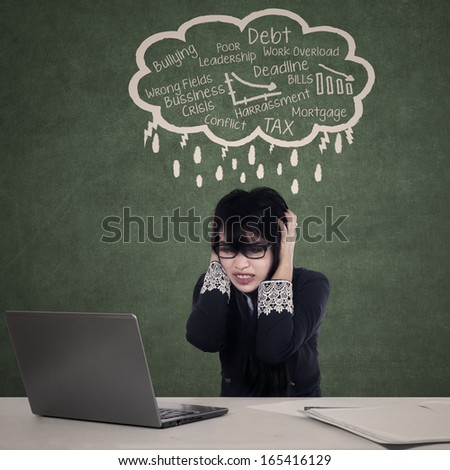 Young businesswoman sitting in front of her laptop worry about the debt crisis  - stock photo