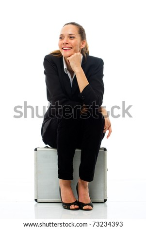 Young businesswoman sitting on a briefcase on white background studio - stock photo