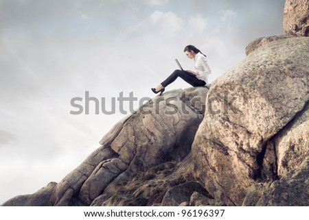 Young businesswoman sitting on a peak in the mountains and using a laptop - stock photo