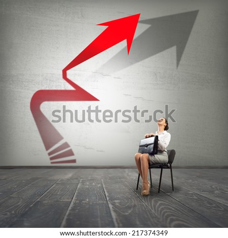Young businesswoman sitting on chair and looking at increasing arrow - stock photo
