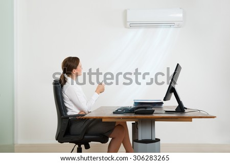 Young Businesswoman Sitting On Chair Using Air Conditioner In Office - stock photo