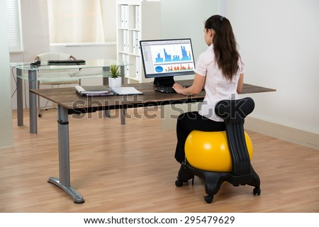 Young Businesswoman Sitting On Fitness Ball While Working On Computer In Office - stock photo