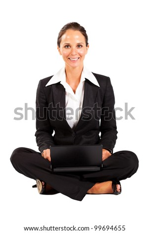 young businesswoman sitting on floor and using laptop - stock photo