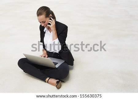 Young businesswoman sitting on floor using laptop and cellphone - stock photo