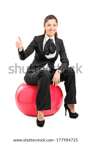 Young businesswoman sitting on pilates ball, giving thumbs up, isolated on white background.