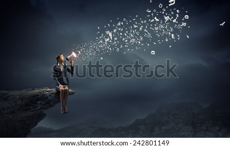 Young businesswoman sitting on rock edge and screaming in megaphone - stock photo