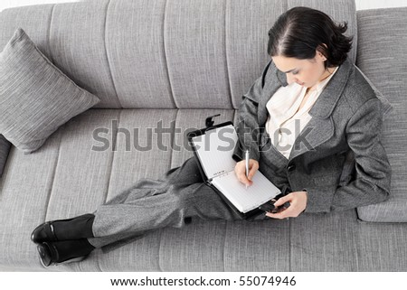Young businesswoman sitting on sofa, working, overhead view. - stock photo