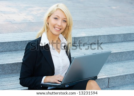 Young businesswoman sitting on stairway, using laptop computer - stock photo