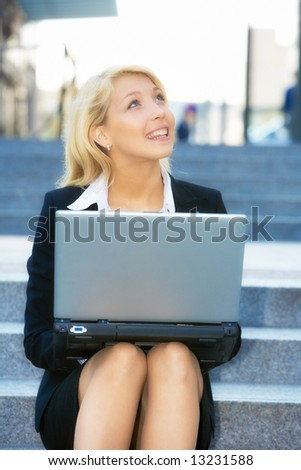 Young businesswoman sitting on stairway, using laptop computer, looking up - stock photo
