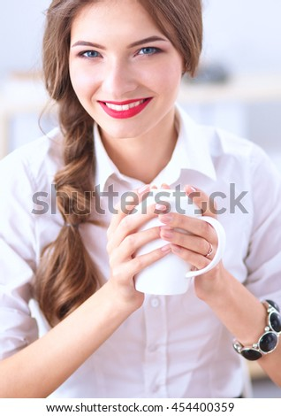 Young businesswoman sitting on the desk with cup in office - stock photo