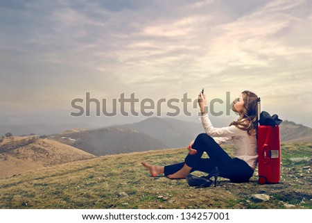 young businesswoman sitting on the grass in the mountain with telephone and trolley - stock photo