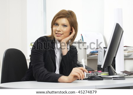 Young businesswoman sitting on workplace with computer