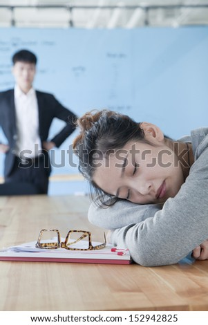 Young businesswoman sleeping during meeting, disappointed Boss looking at her - stock photo