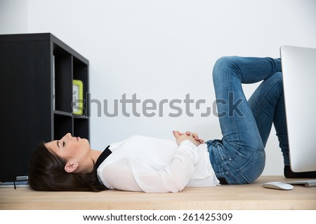 Young businesswoman sleeping on the table in office