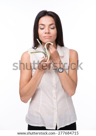 Young businesswoman smelling moneywith closed eyes isolated on a white background - stock photo