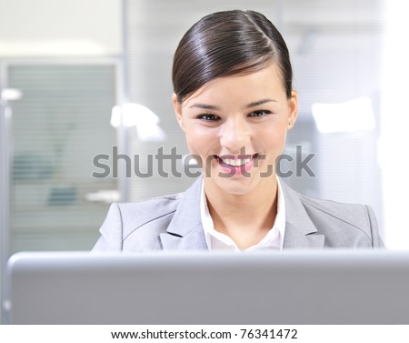 Young businesswoman smiles while working on a computer. Horizontal shot. - stock photo