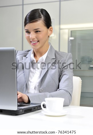 Young businesswoman smiles while working on a computer. Vertical shot. - stock photo