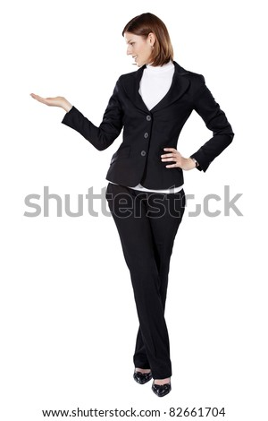 Young businesswoman smiling and holding something in her right hand - stock photo