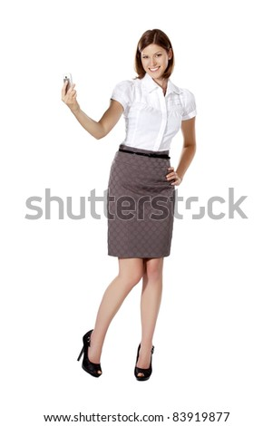 Young businesswoman smiling and taking picture of herself with her phone - stock photo