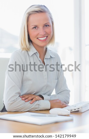 Young businesswoman smiling at camera at her desk - stock photo