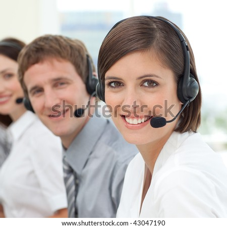 Young businesswoman smiling at the camera in a call center - stock photo