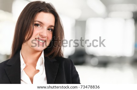 Young businesswoman smiling. Bright blurred background. - stock photo