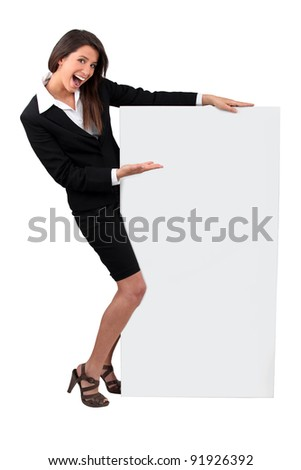 Young businesswoman smiling holding message board - stock photo