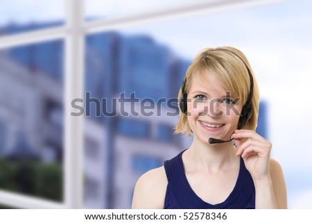 Young businesswoman smiling talking with headset near a window of office - stock photo