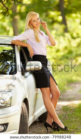 Young businesswoman speaking on mobile phone, leaning against her new car - stock photo