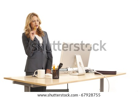 Young businesswoman standing at desk - stock photo