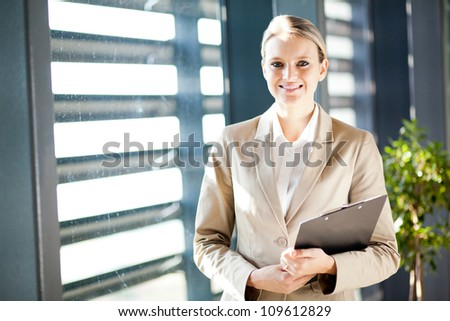 young businesswoman standing by office window - stock photo