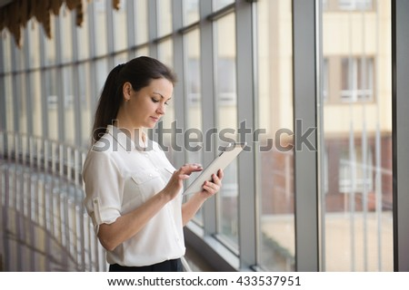 Young businesswoman standing by window in office. Beautiful young female model in bright office.