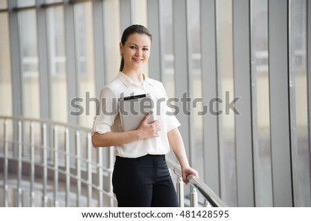 beautiful bright office. young businesswoman standing by window in office beautiful female model bright e