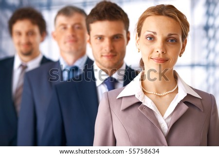 Young businesswoman standing first in the row of business people.