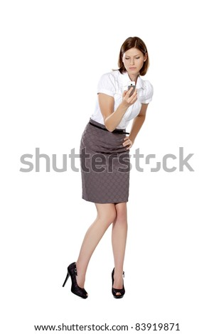 Young businesswoman standing, holding cell phone and looking at it