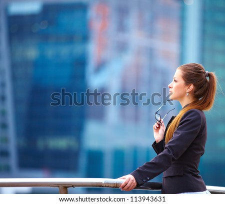 young businesswoman standing in front of office buildings with glasses in her hand - stock photo