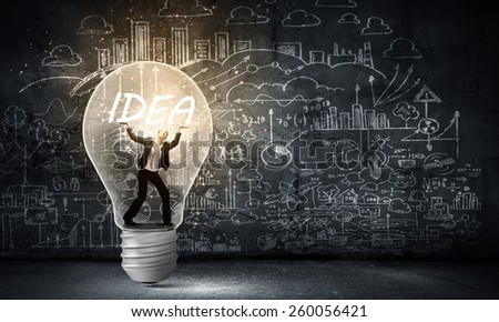 Young businesswoman standing inside of light bulb - stock photo
