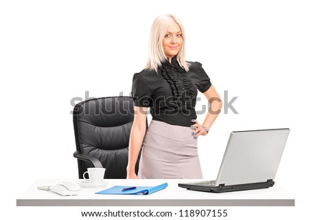 Young businesswoman standing next to desk with laptop isolated on white background - stock photo