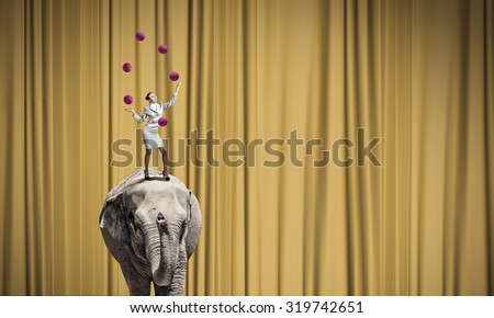 Young businesswoman standing on elephant and juggling with balls - stock photo