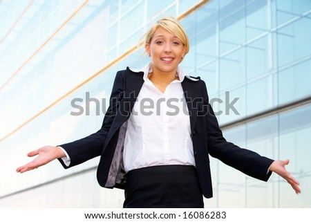 Young businesswoman standing with arms open outside office building - stock photo