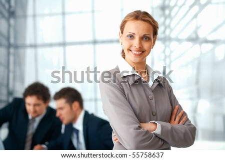 Young businesswoman standing with folded hands, her colleagues at the background. - stock photo