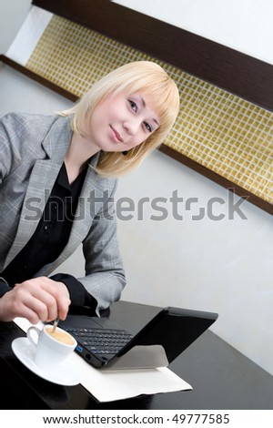 young businesswoman stirs coffee in cup at table with netbook - stock photo