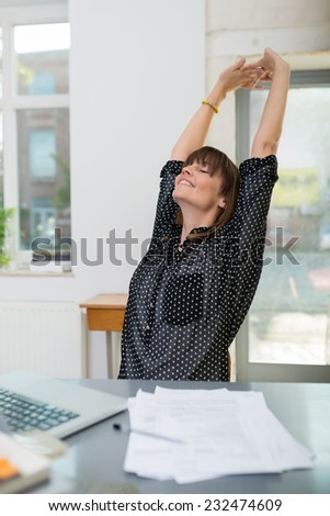 Young businesswoman stretching as she takes a break sitting back in her chair at the office with her hands raised and eyes closed in pleasure - stock photo