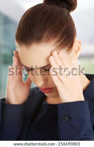 Young businesswoman suffering a headache - stock photo