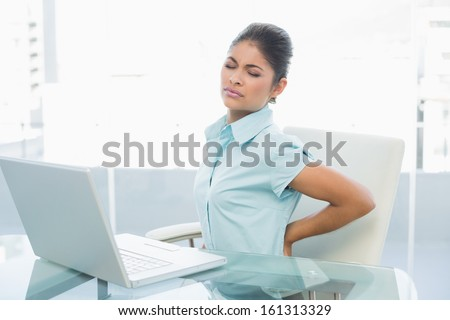 Young businesswoman suffering from back ache in front of laptop in the office - stock photo