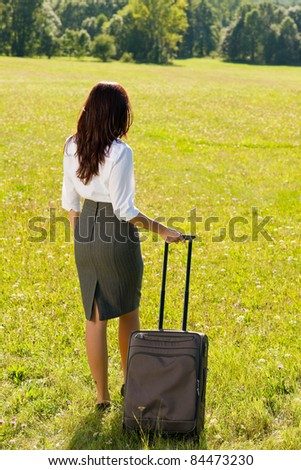 Young businesswoman sunny meadows attractive with suitcase luggage