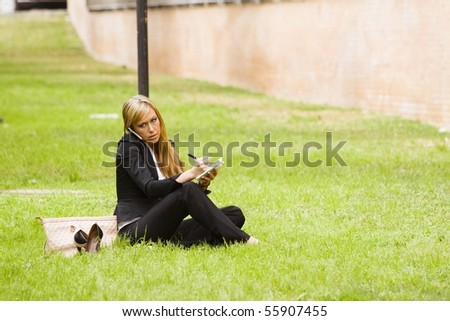 young businesswoman taking notes while talking on the phone - stock photo